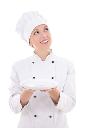 young dreaming woman chef in uniform holding empty plate isolated on white background photo
