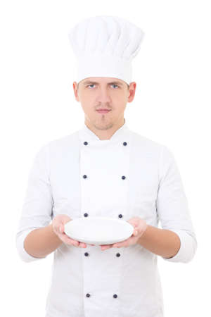 young man chef  in uniform showing empty plate isolated on white background photo