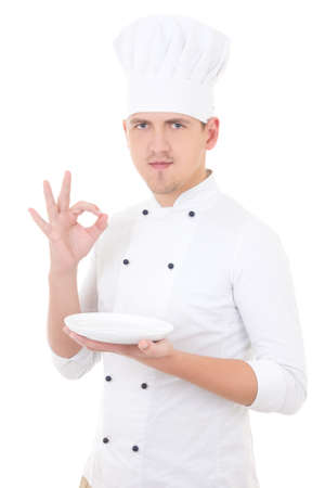 young man chef  in uniform showing ok sign and empty plate isolated on white background photo