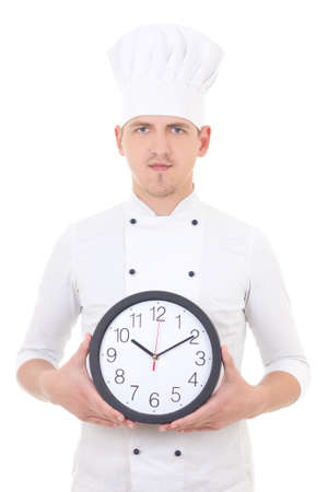 young man chef in uniform holding office clock isolated on white background photo