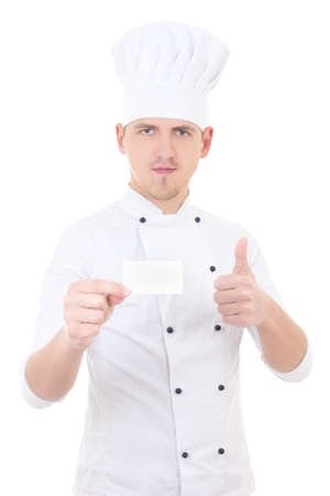 young man chef  in uniform thumbs up and showing blank visiting card isolated on white background photo