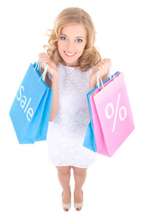 sale concept - funny girl in white dress with shopping bags isolated on white background photo