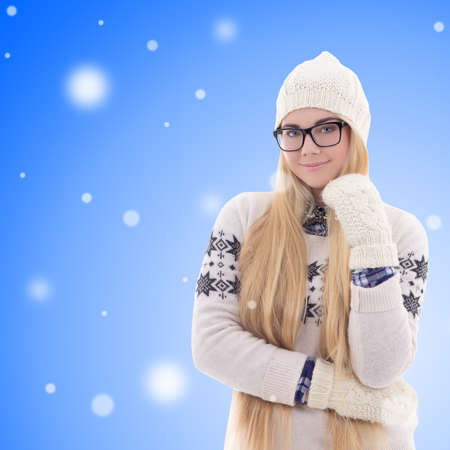 portrait of happy young woman in warm winter clothes over christmas background photo
