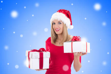 portrait of young happy woman in santa hat posing with gift boxes over christmas background photo