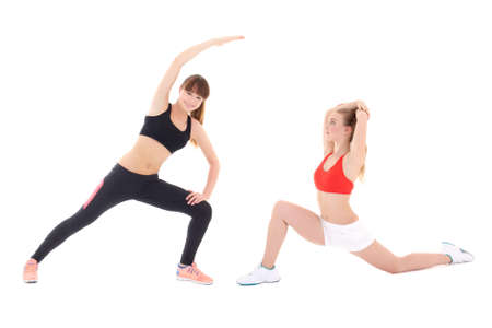 two slim sporty women doing stretching exercises isolated on white background photo