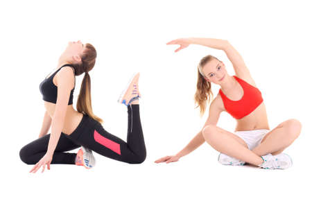 two young beautiful women in sports wear stretching isolated on white background photo