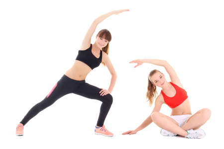 two young sporty women doing stretching exercise isolated on white background photo