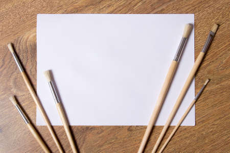 paint brushes and sheet of white paper on wooden background photo