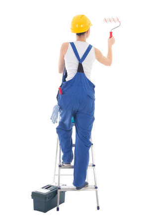 back view of young woman painter in blue coveralls standing on ladder isolated on white background
