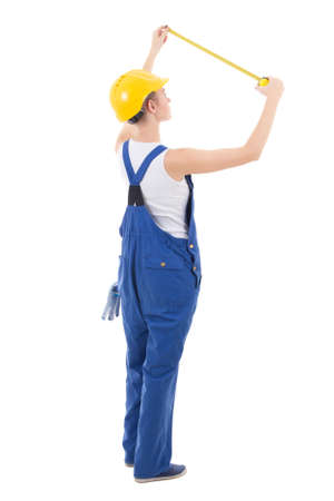 workwear: back view of woman builder in workwear measuring something with measure tape isolated on white background