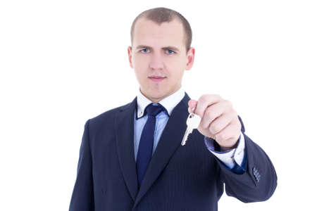 young man real estate agent holding key in hand isolated on white background photo