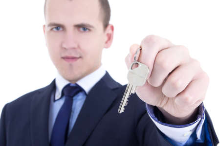 close up of metal key in male real estate agent hand isolated on white background photo