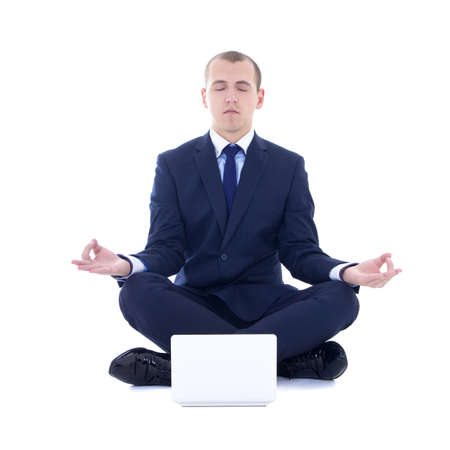 young business man sitting in yoga pose with laptop isolated on white background photo