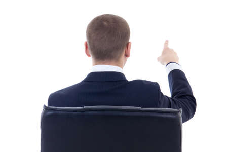 looking behind: back view of business man sitting on office chair and pointing at something isolated on white background