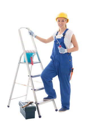 scaling ladder: young woman painter in blue builder uniform with ladder and tools isolated on white background