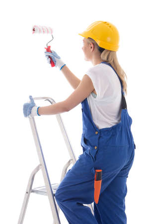 scaling ladder: young woman painter in blue builder uniform standing on ladder with paint brush isolated on white background Stock Photo