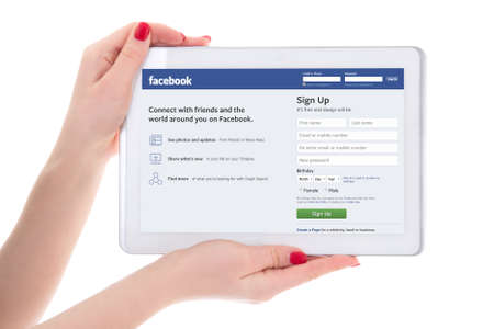 editorial image - tablet pc with facebook page on screen in female hands isolated on white background Editorial