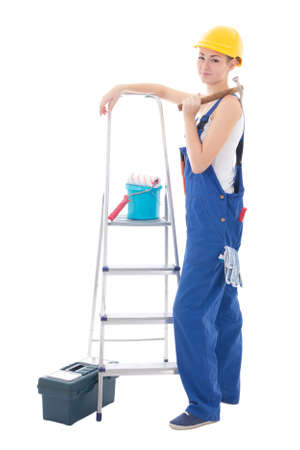 young woman in blue coveralls with builders tools and ladder isolated on white background photo