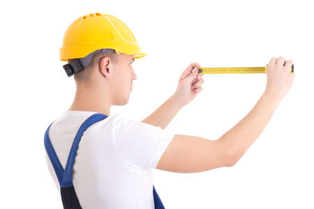 back view of man builder in blue coveralls holding measure tape isolated on white background photo