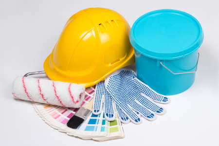 painters tools - brushes, work gloves, helmet and bucket of paint over white background photo