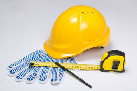 builders tools - helmet, work gloves, pen and measure tape  over white background photo