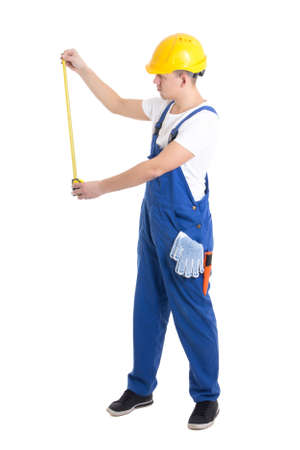 side view of man builder in blue coveralls holding measure tape isolated on white background photo