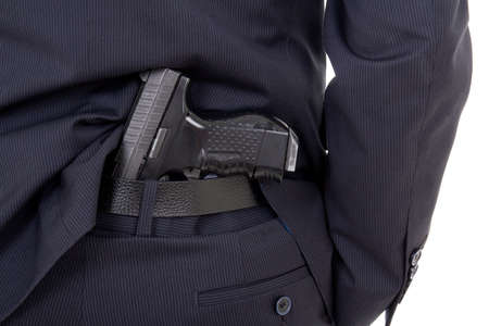 concealed: close up of gun in business suit pants isolated on white background