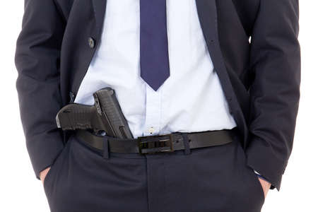 detective, policeman or bodyguard with gun in pants isolated on white background photo