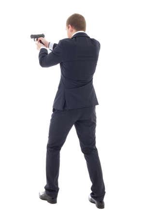 hombre disparando: Vista trasera del hombre agente especial en traje de negocios posando con pistola aislado en fondo blanco