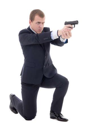 agent de sécurité: homme en costume d'affaires assis sur le genou et le tir avec un pistolet isolé sur fond blanc Banque d'images