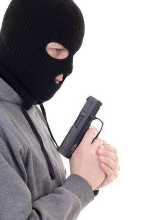 assasin: profile view of criminal man in mask holding gun isolated on white background Stock Photo