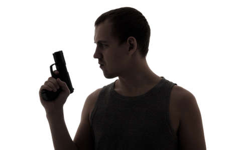 assasin: silhouette of criminal man holding gun isolated on white background Stock Photo