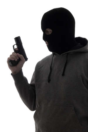 assasin: dark silhouette of criminal man in mask holding gun isolated on white background