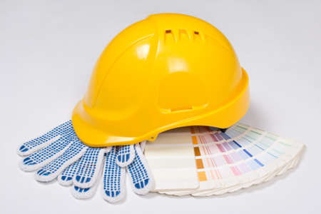 builders yellow helmet, work gloves and colorful palette over white background photo