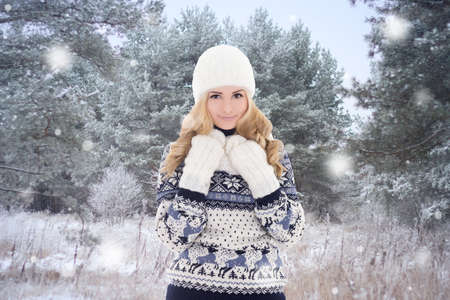 pretty woman in warm clothes posing in winter forest photo