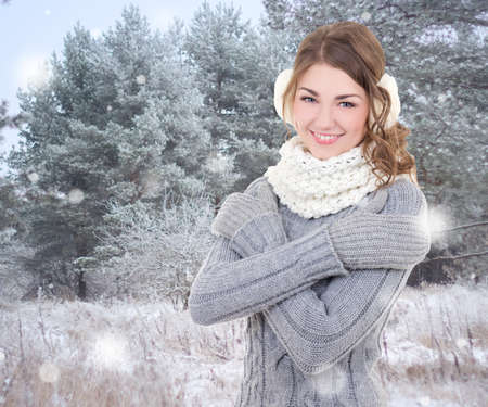 muff: portrait of young beautiful woman in winter forest