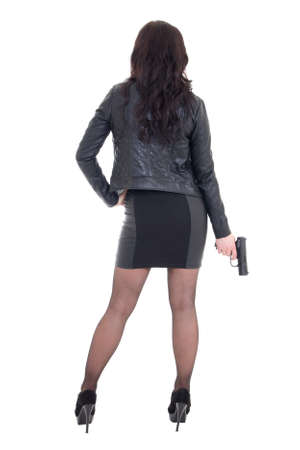 leather coat: back view of sexy woman in black holding gun isolated on white background