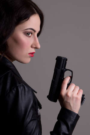 sexy woman in black with gun over grey background
