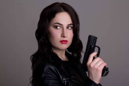 portrait of young beautiful woman with gun over grey background Stock Photo