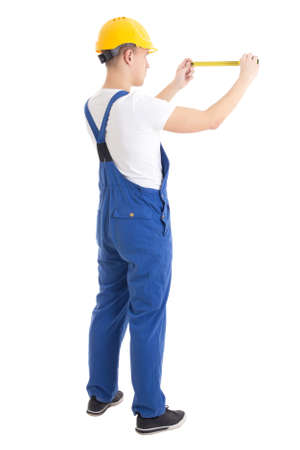 back view of man builder in blue uniform holding measure tape isolated on white background photo
