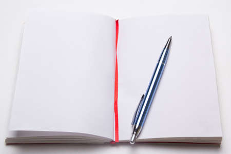 open note book with empty pages with pen on the table photo