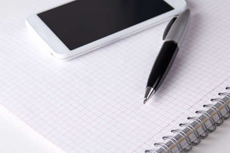 close up of note book with checked pages, pen and smart phone photo