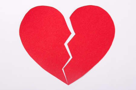 heartbreak issues: love concept - red paper broken heart over white background Stock Photo
