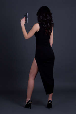 back view of sexy woman secret agent posing with gun over grey background