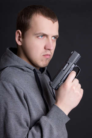 assasin: young man criminal with gun over grey background