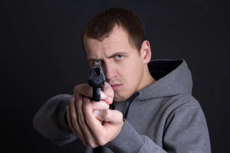 assasin: man criminal aiming with gun over grey background