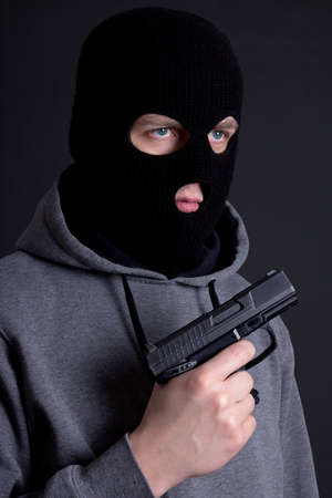 assasin: man criminal in black mask with gun over grey background