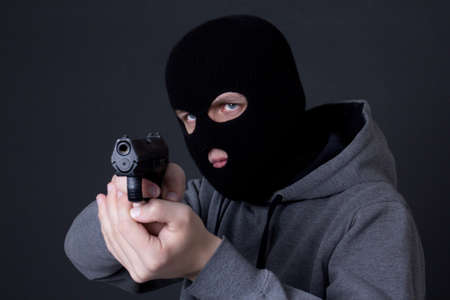 assasin: man criminal in black mask aiming with gun over grey background