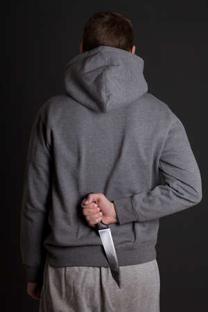 man hiding knife behind his back over grey background photo