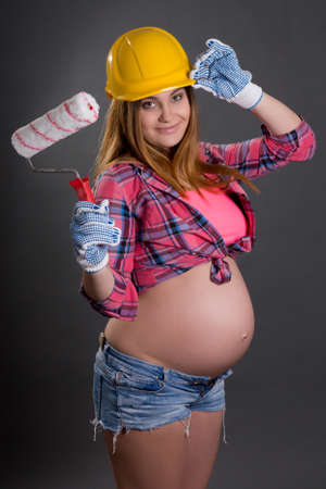young beautiful pregnant woman in builder's helmet with  paint brush over grey background photo
